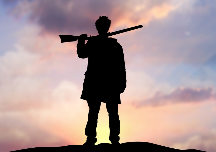 Silhouette of a man with a rifle against a cloudy sunset | Cloud Surfing Media Digital Marketing